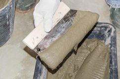 Tiler taking tile adhesive with a notched trowel Stock Photography