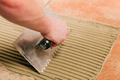 Tiler tiling tiles on the floor Stock Photo