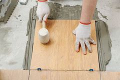 Tiler is using a rubber hammer. Royalty Free Stock Photography