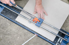 Tiler using a tile cutter Stock Photos