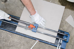 Tiler using a tile cutter Royalty Free Stock Images