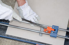 Tiler using a tile cutter Royalty Free Stock Image