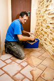 Tiler at work. A man tiler working at a new floor tiles, cleaning them with water Stock Images