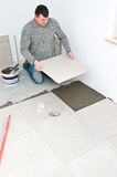Tiler at work. Placing a large square tile on the floor of a new home room Royalty Free Stock Photos