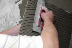 Tiler at work bonding of floor  tile adhesive Royalty Free Stock Photos