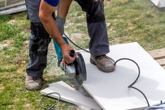Tiler at work. A tiler at work. cuts plates with a cut-off wheel royalty free stock images