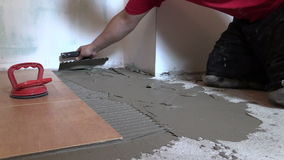 Tiler worker hand spread adhesive material. Right side sliding stock footage