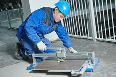 Tiler working with tile cutting equipment Royalty Free Stock Images