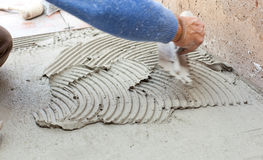 Tiler works with flooring. Royalty Free Stock Photos