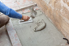 Tiler works with flooring. Stock Photography