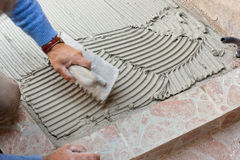 Tiler works with flooring. Royalty Free Stock Photography