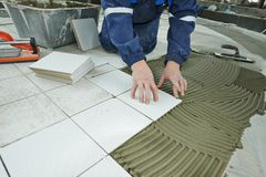 Tilers at industrial floor tiling renovation Royalty Free Stock Images