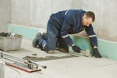 Tilers at industrial floor tiling renovation Stock Photos