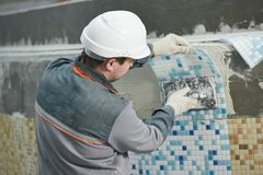 Tilers at industrial floor tiling renovation. Industrial tiler builder worker installing floor tile at repair renovation work Royalty Free Stock Image
