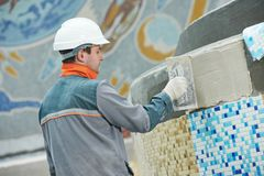 Tilers at industrial floor tiling renovation. Industrial tiler builder worker installing floor tile at repair renovation work Royalty Free Stock Photography