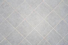 Tiles. Square regular gray tiles. A floor detail Royalty Free Stock Photo