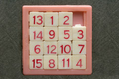 Tiles. Children's party favor number puzzle in pink stock image