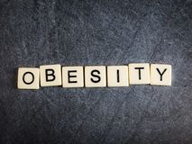 Letter tiles on black slate background spelling Obesity stock image