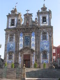 Tiles in a Church in Porto, Portugal. The  facade with two towers, bells, a cross and blue tiles of a baroque church in Porto, Portugal Royalty Free Stock Photos