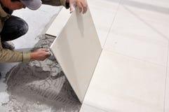 Tiles installation. Image of a man installing ceramic floor Royalty Free Stock Photos