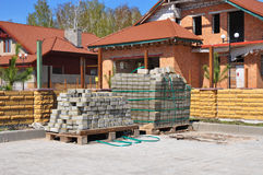 Tiles Paving Ready to Install against House Construction. Road Construction from Paver Bricks Royalty Free Stock Photo