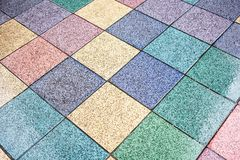 Floor  with colored tiles in yellow, blue,green,pink,. Tiles of purple, red, blue colors  on the outdoor street with colorful that motivates the joy Royalty Free Stock Photography