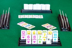 Tiles in rack and gameplay in Rummy on table. Tiles in rack and gameplay in Rummy tile-based card game on green baize table. Rummy is tile and card game based on stock image