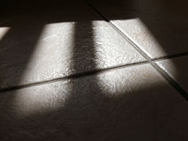 Tiles and shadows. Sunlight reflected on floor tiles Royalty Free Stock Photography