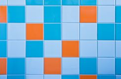Tiles on wall in light blue, azure blue and orange. Part of wall in bathroom with tiles in light blue, azure blue and orange Stock Image