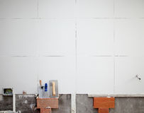 Tiles white wall contruction with trowels tools Stock Photography