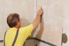 Tiling. Man installs ceramic tile Stock Photo