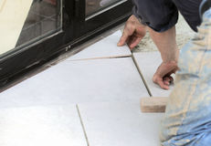 Tiling a floor tile. Craftsman is tiling a floor tile to arrange the surface Royalty Free Stock Photos