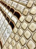 Tiling That Looks Like Library Books Stacked with Fleur De Lis Design. Retro looking ceramic tile that shows book ends stacked and surrounded by square tiling Stock Image