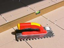 Tiling tools. Trowel and long level on new tiled floor Stock Images