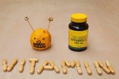 Tillägg skorrar och ett vitamintecken som skapas från vitaminpreventivpillerar Royaltyfri Foto