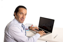 40 till 50 år gammal hög affärsman som arbetar på datoren på kontorsskrivbordet som ser säkert och avkopplat Arkivbild