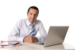 40 till 50 år gammal hög affärsman som arbetar på datoren på kontorsskrivbordet som ser säkert och avkopplat Royaltyfri Bild