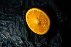 Till hälften en apelsin på en mörk bakgrund royaltyfri fotografi