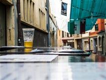 Till hälften färdigt öl på en kafétabell Royaltyfri Bild