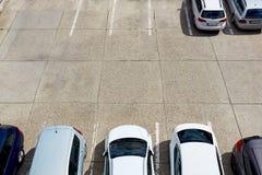 Till hälften tom parkeringsplats med bilar Royaltyfri Bild