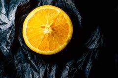 Till h?lften en apelsin p? en m?rk bakgrund arkivbild