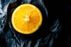 Till h?lften en apelsin p? en m?rk bakgrund royaltyfria foton