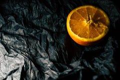 Till h?lften en apelsin p? en m?rk bakgrund royaltyfri fotografi
