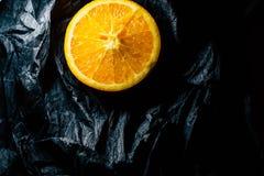 Till h?lften en apelsin p? en m?rk bakgrund royaltyfri bild
