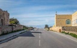 Till horionen En tom ojämn gata till horisonten som inramas av några byggnader i Malta, på en molnig dag royaltyfria bilder
