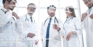 Till och med exponeringsglaset en grupp av doktorer som står i kontoret royaltyfri bild