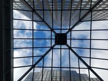 Till och med taket som ser rakt upp till och med exponeringsglashjärtförmaktaket på skyskrapor royaltyfri bild