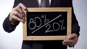 80 till 20 procent skriftligt på svart tavla, hållande tecken för man, Pareto princip Royaltyfri Foto
