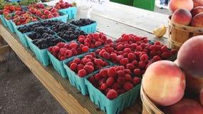 Till salu sommarbär och persikor arkivfoto
