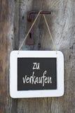 Till salu tecken på en trädörr med tysk text Royaltyfri Bild